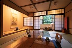 A large window overlooks the pond and autumnal forest.