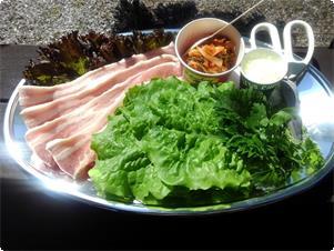 サムギョプサルセット 厚切り豚肉をバーベキューコンロで焼いて お好みの大きさに・・・ キムチ・大葉・セロリスプラウト・玉ねぎの酢漬けと一緒に サンチュに巻いてお召し上がりください。  3~4名用 2800円