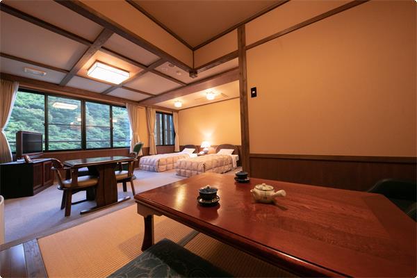 広い窓から池と対岸の紅葉林を見渡せる本館和洋室は、  ベッドが二つと奥に4畳の座敷がございます。 玄関から客室、大浴場、お食事処へエレベーター利用のみで行くことができます。 バリアフリー対応可能となっております。 ※ベッドは2台、3名ご宿泊の場合は、一枚お布団を追加させて頂きます。