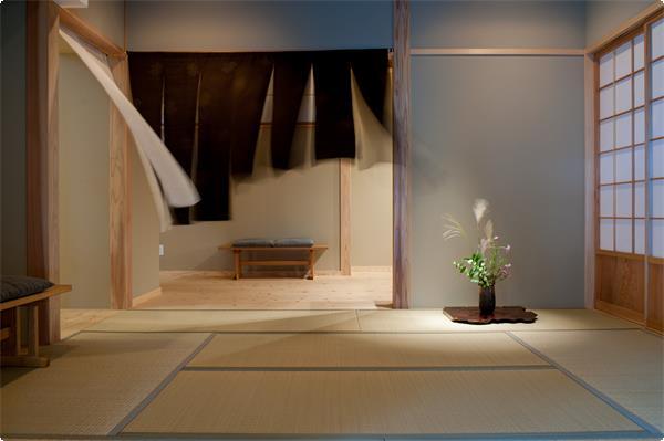 <施設ガイド>『取次の間』  土間で履物を脱いで邸内に上がります。潮風に吹かれた結城紬の暖簾の先に寛ぎの邸内空間が広がります。